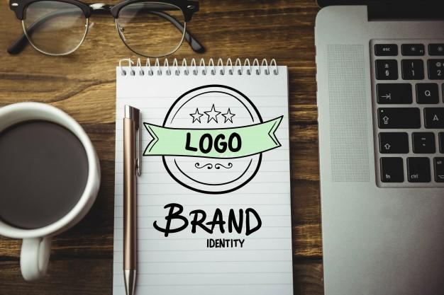 Un cuadernos con el diseño de un logotipo junto al portátil